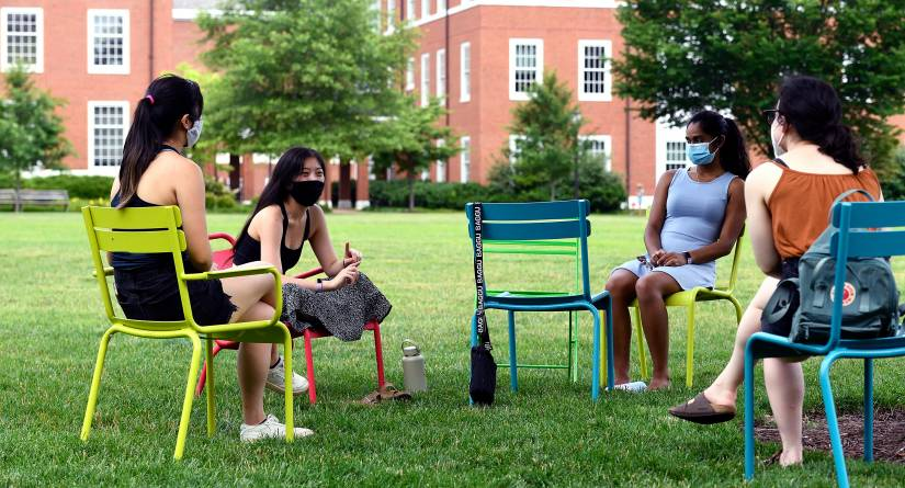 Four socially distanced students sit and talk on a campus quad