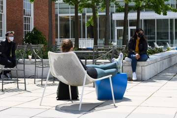 Three socially distanced students talk on a campus patio
