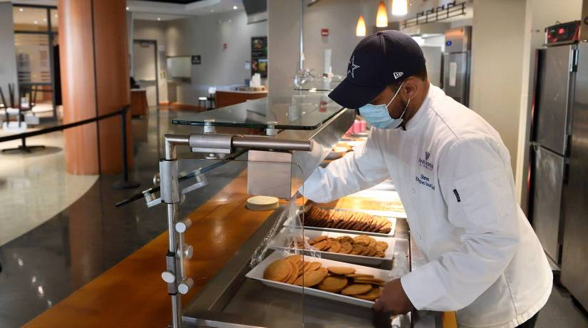 Man places tray of cookies in dining hall