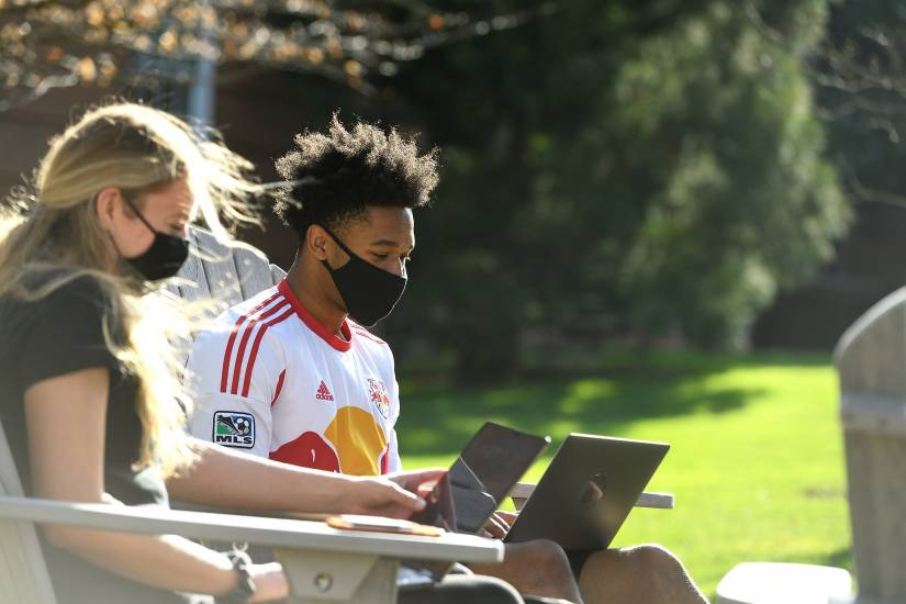 Two students wearing face coverings study outdoors using laptops