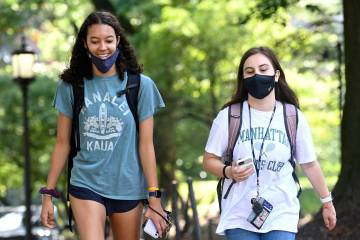Two students walk side by side on campus